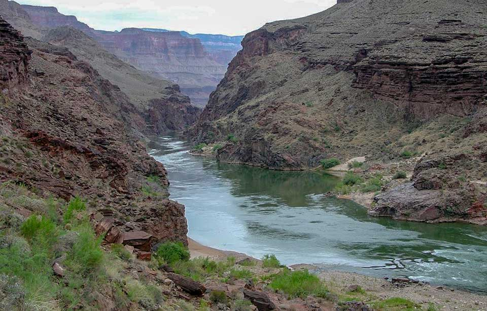 A calm, green river with rocky cliffs on either side, and a sandy beach in the foreground. USGS photo.