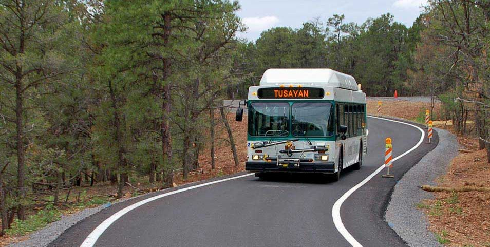 a white bus with green trim is driving on a bypass lane through a wooded area.