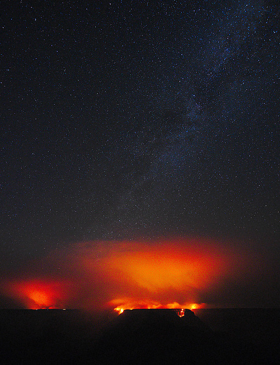 Light from wildfire flames illuminating the smoke above with an orange glow. Stars of the milky way in the dark sky above.