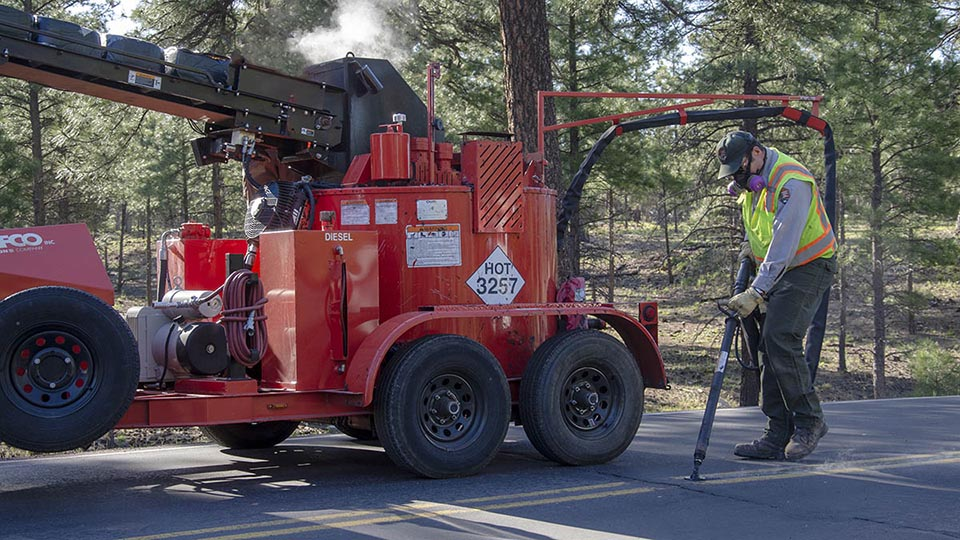 NPS road repair worker is sealing roadway cracks with an asphalt wand behind a large, red asphalt melting trailer.
