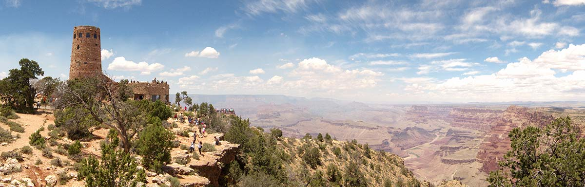 Expansive landscape of Grand Canyon on a hazy summer day. On the far left, the stone watchtower with many tourists walking around the canyon rim.