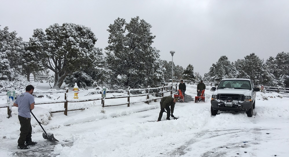 Maintenance workers clearing snow from parking area.