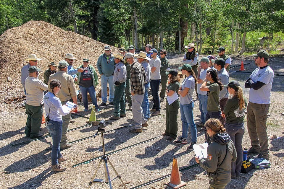 a group of around two dozen park employees gathered around in a circle and attending a morning work briefing.