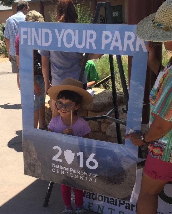 A Grand Canyon Jr. Ranger poses with a Find Your Park sign