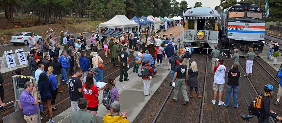 Colorful crowd of people at train depot listening to speeches. Two trains are on the right and to the left of trains is a row of exhibitor tents.