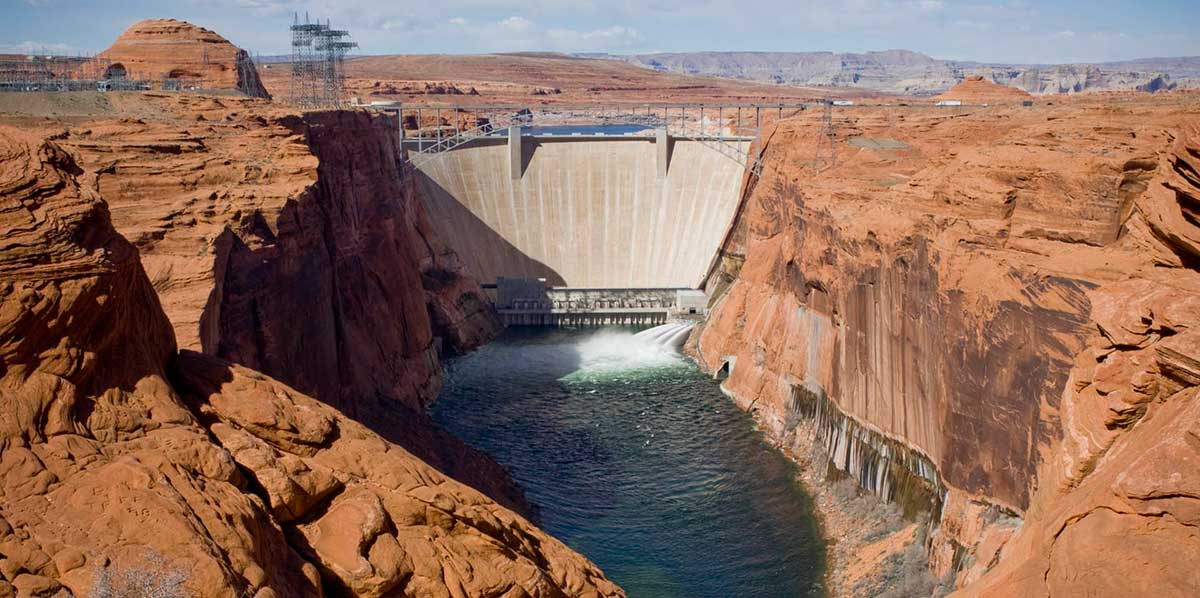 View upriver past beige colored sandstone cliffs on either side of Glen Canyon Dam. The water tubes at the bottom of the white , wedge-shaped dam are open and are discharging water jets for a high-flow event into the green-colored Colorado River.