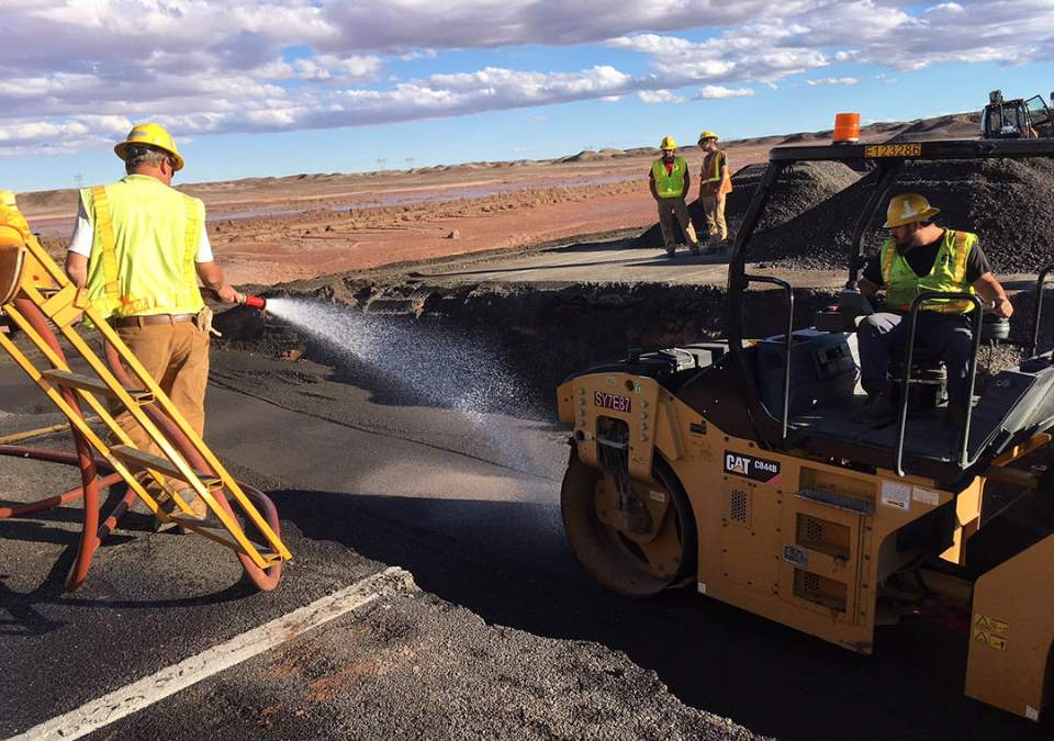 Several workers wearing yellow safety vests and helmets are cleaning up a section of paved highway that has washed away.