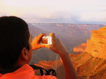 youth photographing sunset at canyon