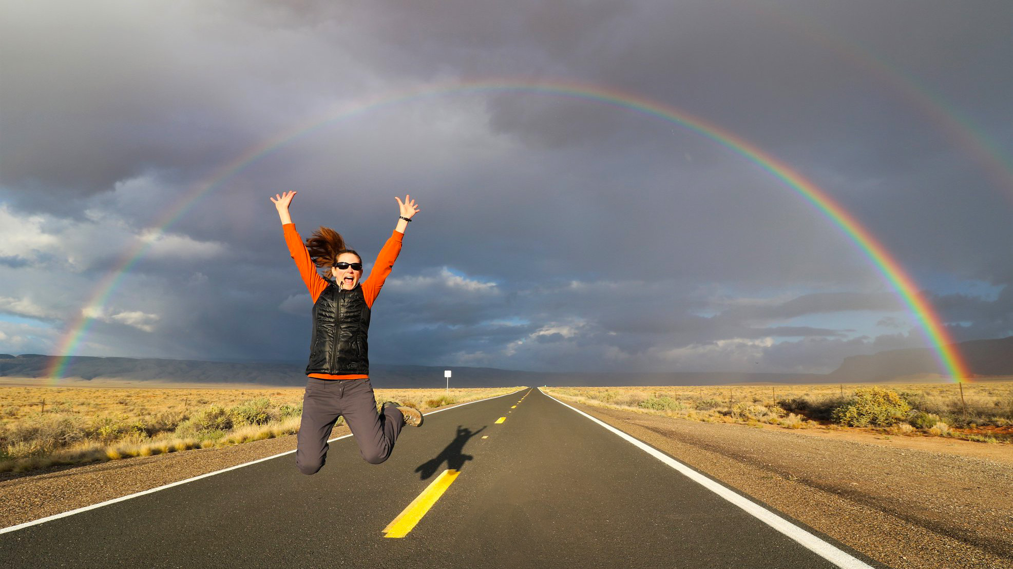 A woman is jumping for joy above a two-lane highway through a desert landscape. A full rainbow crosses the sky in a semicircular arc.