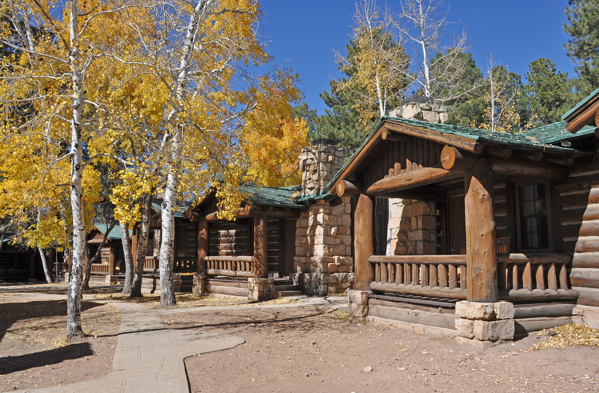 several rustic log and stone lodge buildings surrounded by aspen trees with brilliant yellow leaves.
