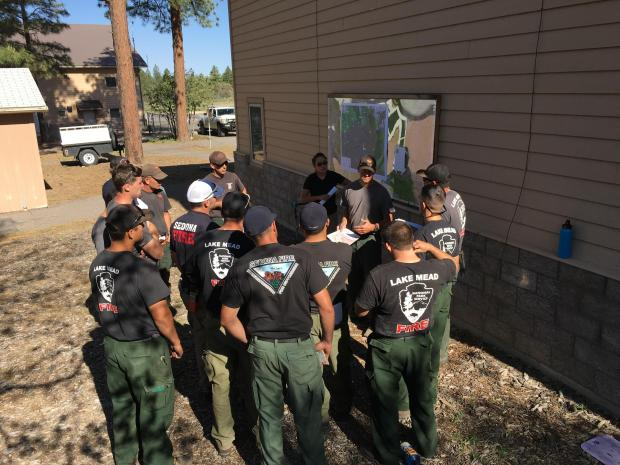 14 firefighters discuss the day's operations in front of a map