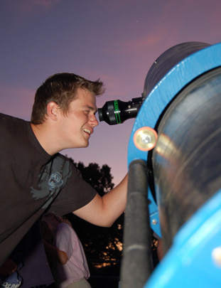 Young man enjoying the stars through a telescope.