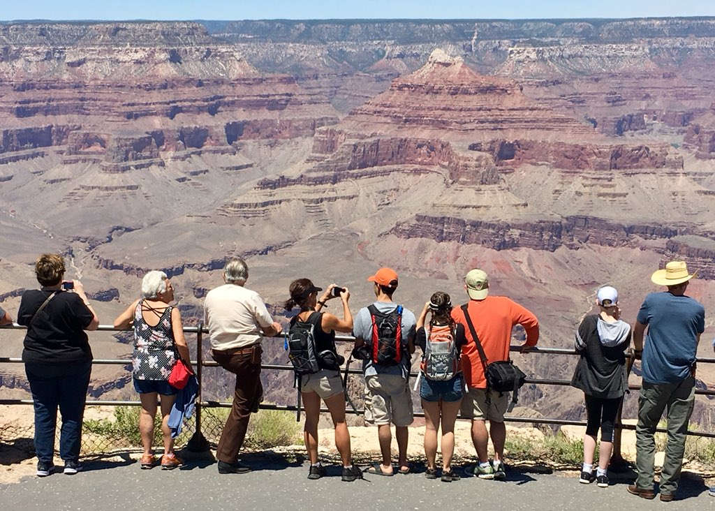 Eight Grand Canyon visitors wearing summer clothing are standing at scenic overlook behind a railing. A desert canyon landscape is in the distance.
