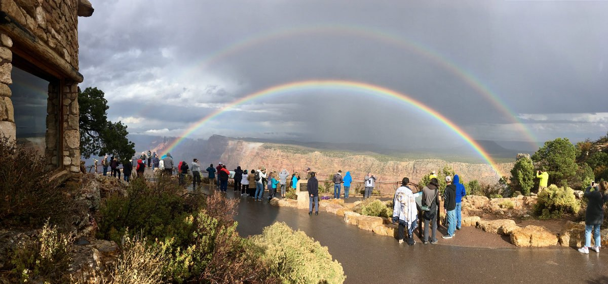 A group of sightseers standing on a wet sidewalk at a scenic overlook. In the distance a double rainbow forms a complete arc across the sky, appearing in front of a sheer cliff.