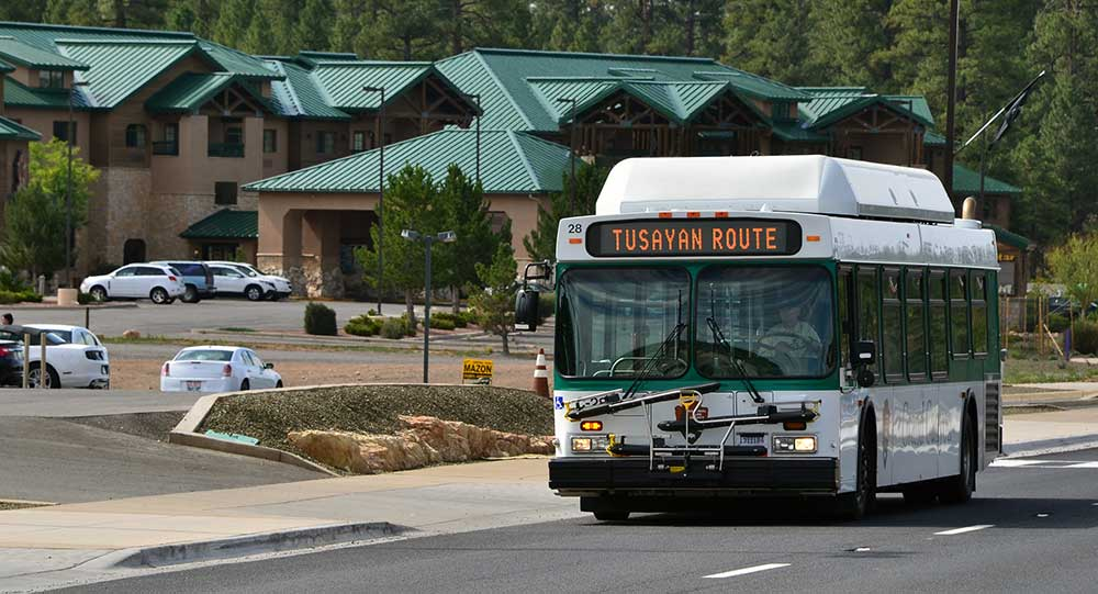 "a white and green bus with a marque reading ""Tusayan Route,"" driving past a large hotel several stories high with a green metal roof."