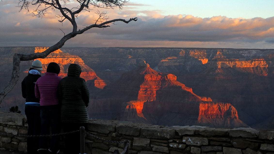 Three people wearing heavy winter coats are watching reddish sunrise light illuminating peaks and cliffs within a canyon landscape