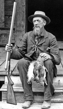 Capt. John Hance sitting on the steps with his rifle and 2 dead squirrels.
