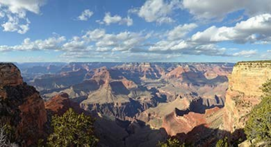 a view looking out across Grand Canyon on a sunny day with clouds in the distance.