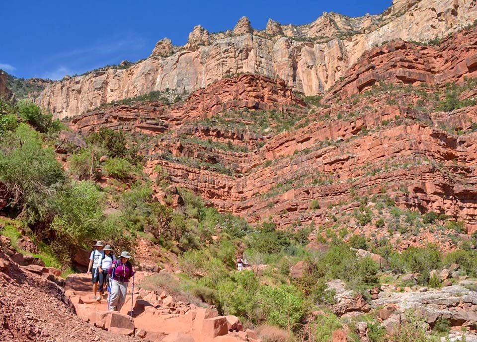 three hikers have descended several thousand feet into a canyon on a backcountry trail, and layered and colorful cliffs tower above them.