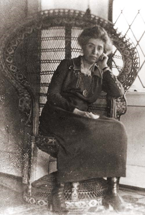 Full length photo of Mary Colter sitting in an elaborate wicker chair that wraps around her.