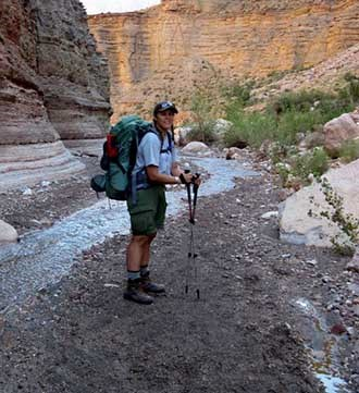 Ranger Sara poses on a backpack along a small creek.