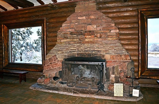 Against a log cabin style wall, a stone fireplace made from layers of rock strata is centered between two picture windows.