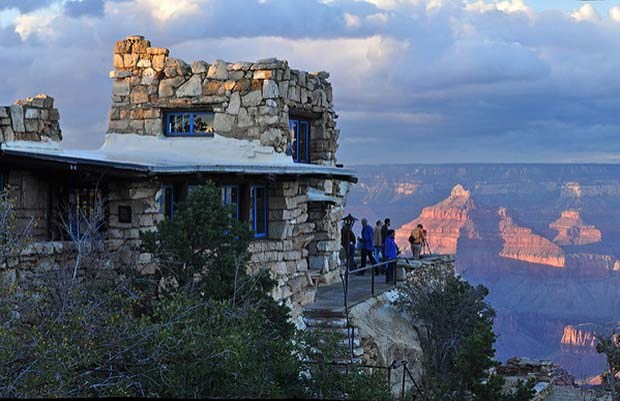 square stone building with blue window frames on canyon's edge. Several people on porch viewing sunset on distant peak.