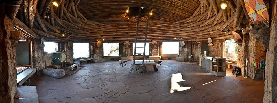 A wide open circular room with a flagstone floor. Large picture windows take up about 2/3 of the circumference of the circle. Windows are separated by stone pillars. The ceiling is made up of inter-woven logs that surround, then arch over the round room.