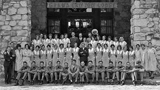 Large group of lodge employees posing by the front entrance.