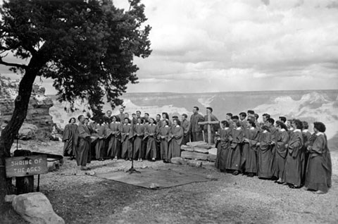 A choir wearing robes on either side of a stone altar and wooden cross. The Grand Canyon landscape is behind the choir.