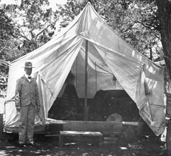 JOHN GEORGE VERKAMP STANDING BY  HIS TENT/CURIO STORE. 1897