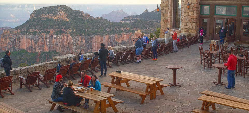 Viewing sunset in Grand Canyon from the outdoor veranda of Grand Canyon Lodge on North Rim.  Flagstone floor with row of chairs just behind the guard wall and several visitors are viewing the canyon. A family is eating dinner at a picnic table.