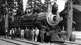 SANTA FE ENGINE 1251 W/ PASSENGER TRAIN BY GRAND CANYON DEPOT, TRAIN & STATION CREW POSING IN FRONT OF LOCOMOTIVE. CIRCA 1915