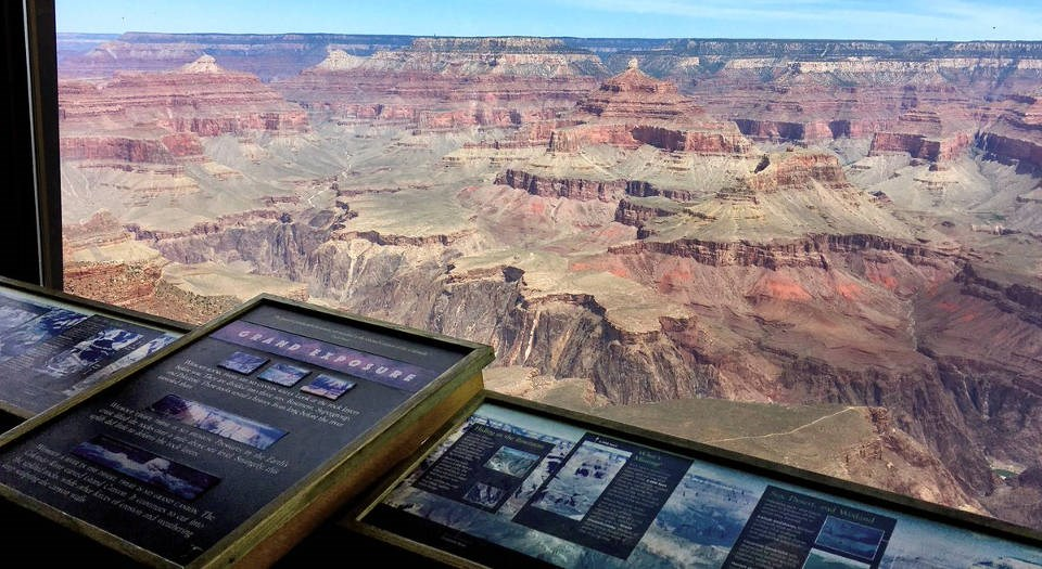 Looking past a row of geologic exhibits with text and photos, through a large glass picture window at a colorful Grand Canyon Landscape.