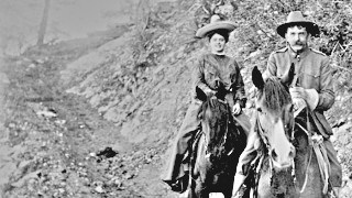 Black and White historic photo of a man and a woman posing on horseback on a trail inside a canyon.