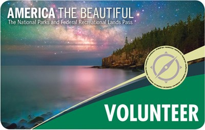 America The Beautiful Volunteer Pass graphic shows rocky, forested shoreline on calm water with Milky Way Galaxy in the sky above.