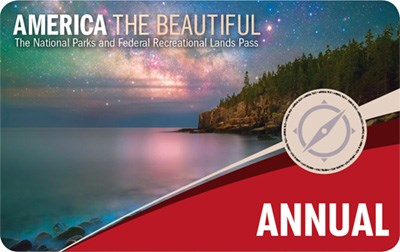 America The Beautiful Annual Pass graphic shows rocky, forested shoreline on calm water with Milky Way Galaxy in the sky above.