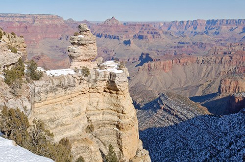 Rounded pale rock formation against Grand Canyon in the background.