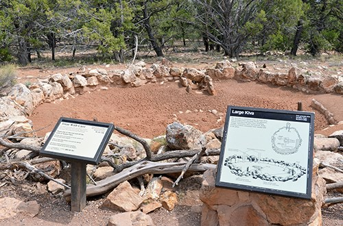 A stone wall circles around bare dirt with pine trees in the background, two informative signs in the foreground.