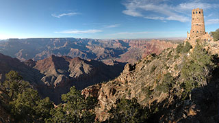 looking across a wide, open expanse of Grand Canyon on the left, with thw watchtower on the far right, perched on the edge of a steep cliff.