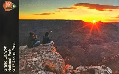 Two people watching sunrise while sitting near the edge of Grand Canyon. One is holding a selfie stick, the other is taking a photo with their smartphone.