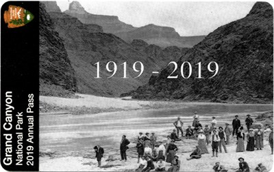 Grand Canyon Nat Park 2019 Annual Pass features a Black and White historic photo of a group of well-dress people on a beach by a river surrounded by canyon walls.