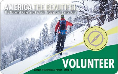 "America the Beautiful 2020 Volunteer Pass shows a skier on a steep slope, the word ""volunteer"" is against a green background."