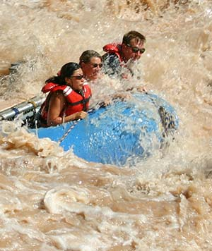 three individuals wearing orange life vests are riding in a blue raft through a muddy river rapid