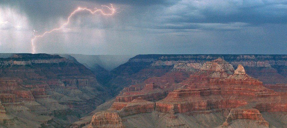 Looking out across the canyon during a storm. A bolt of lightning on the far left hitting the canyon rim on the north side.