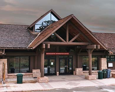 Backcountry Information Center is a modern building built in the rustic style with large windows and a cross-gabled roof that extends out over the entryway. Behind that is a large gabled window that acts as a skylight.