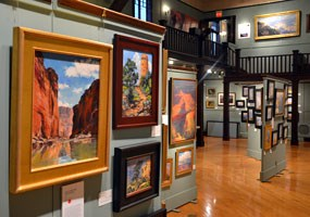 Paintings on display in exhibit hall with sage green walls and wood floors.