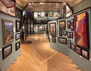 A variety of landscape paintings in an art gallery.
