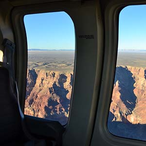 View out two window of a tour aircraft at Grand Canyon. Vermilion colored cliffs are visible.