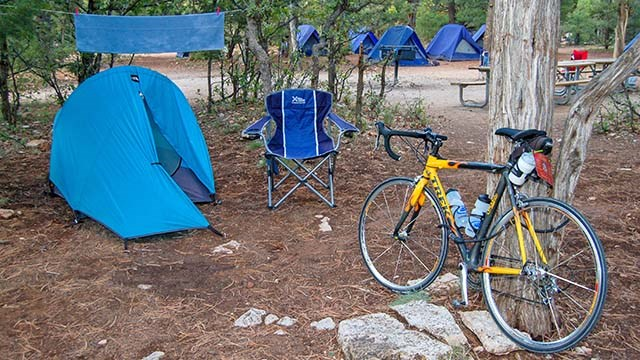 a yellow bicycle next to a tree and a blue tent, with a row of blue tents in the forested background.